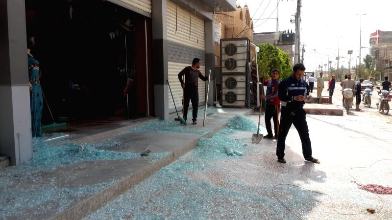 People clean the broken glass of a damaged shop after Iraqi Air Force's bombing in Islamic State (IS) militants-seized city of Fallujah, some 50km west of ...