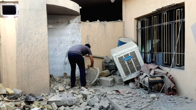 A man inspects a damaged building after Iraqi Air Force bombing in Islamic State (IS) militants-seized city of Fallujah, some 50km west of Baghdad, Iraq, May 1, 2015. ...