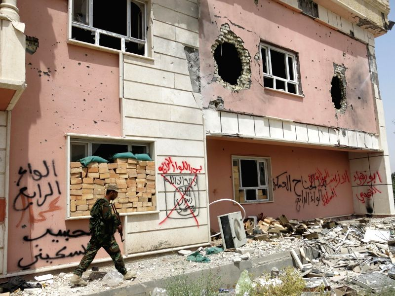 FALLUJAH, May 29, 2016 - A fighter from a Shiite paramilitary units, known as Hashd Shaabi, walks near a damaged building in Harariyat village on the outskirts of Fallujah city in Iraq's western ...