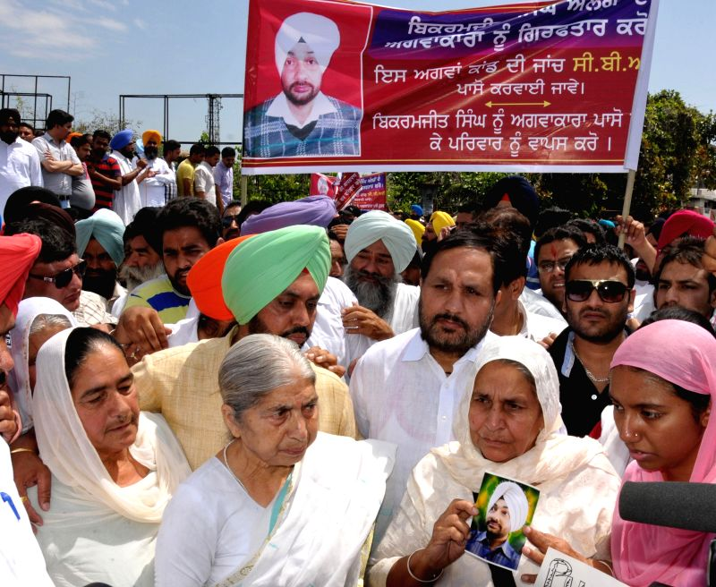 Family members of Bikramjit Singh demonstrate against his murder at Bhandari Bridge in Amritsar on May 14, 2014.