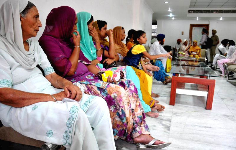 Family members of Indians abducted in Iraq after receiving compensation cheques from Shiromani Gurdwara Parbandhak Committee (SGPC) President Avtar Singh Makkar during a function in Amritsar on July . - Avtar Singh Makkar
