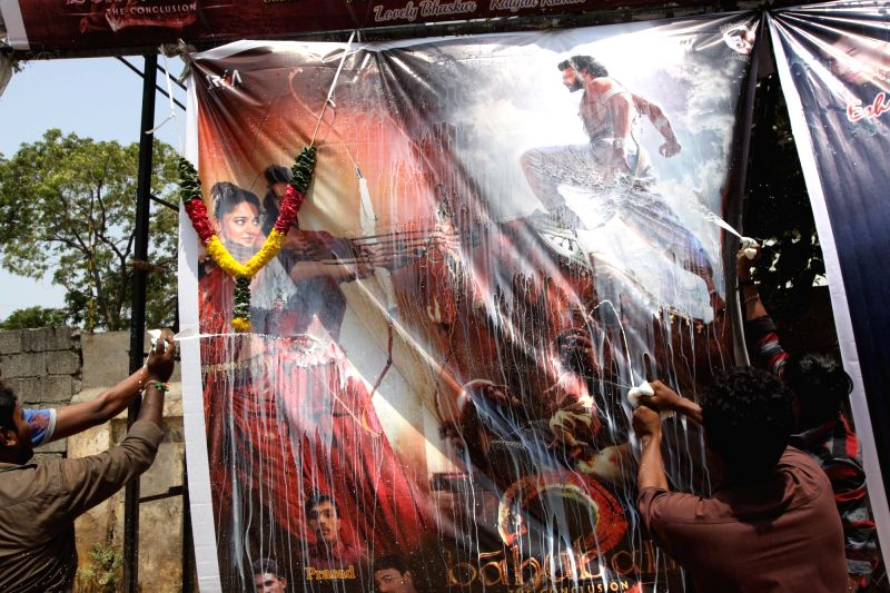 "Fans wash a poster of ""Baahubali 2"" with milk after the film was released in Chennai, on April 28, 2017."