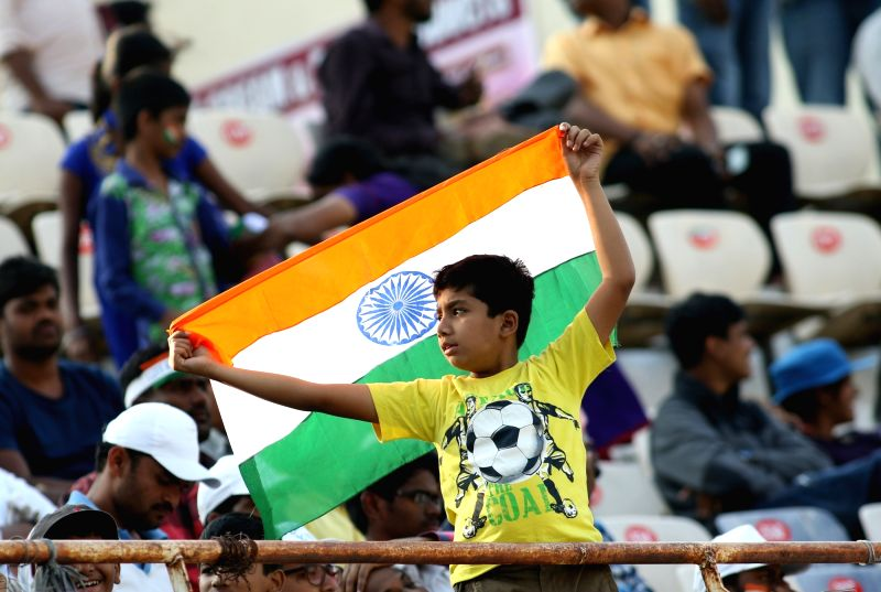 Fans with the Indian flag cheer their team during the test match between India and Bangladesh in Hyderabad on Feb. 11, 2017.