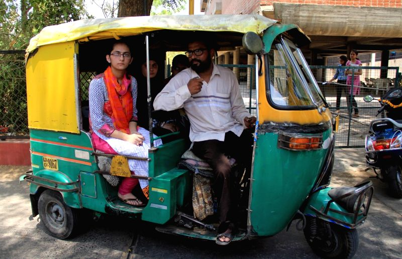 Farhana Bavani, who topped in Class XII exams (Science Stream) conducted by Gujarat Board with her father Farooq Bavani an auto-rickshaw driver by profession in Ahmedabad on May 11, 2017.