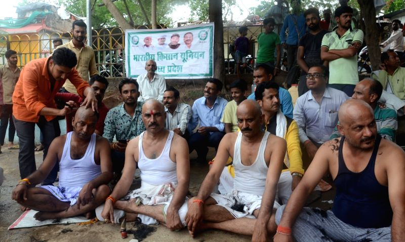 Farmers get their heads shaved  as they stage a demonstration against the state government, in Bhopal on June 10, 2018.