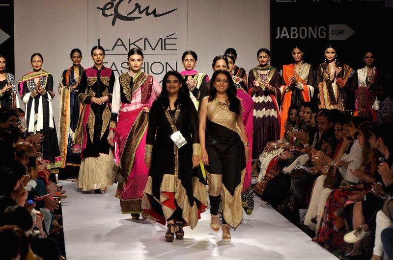 Fashion designers Ekta Jaipuria and Ruchira Kandhari walk with the models during the Lakme Fashion Week (LFW) Winter/ Festive 2014, in Mumbai, on Aug. 22, 2014.