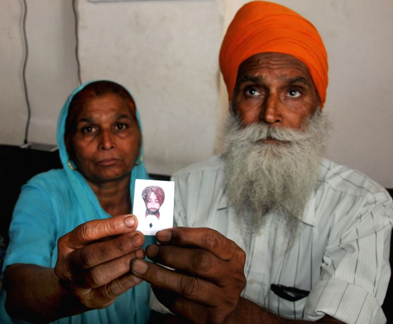 Father and mother of Gurmukh Singh who is believed to be trapped in violence-hit Iraq pray for his well being at the Golden Temple in Amritsar on June 19, 2014. - Gurmukh Singh