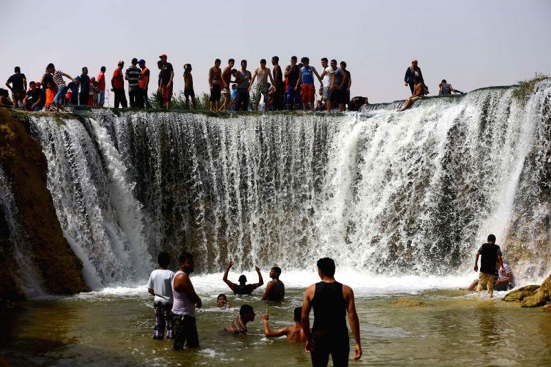 FAYOUM, May 12, 2016 - People amuse at a waterfall in Wadi El-Rayan of Fayoum, Egypt, on May 10, 2016.