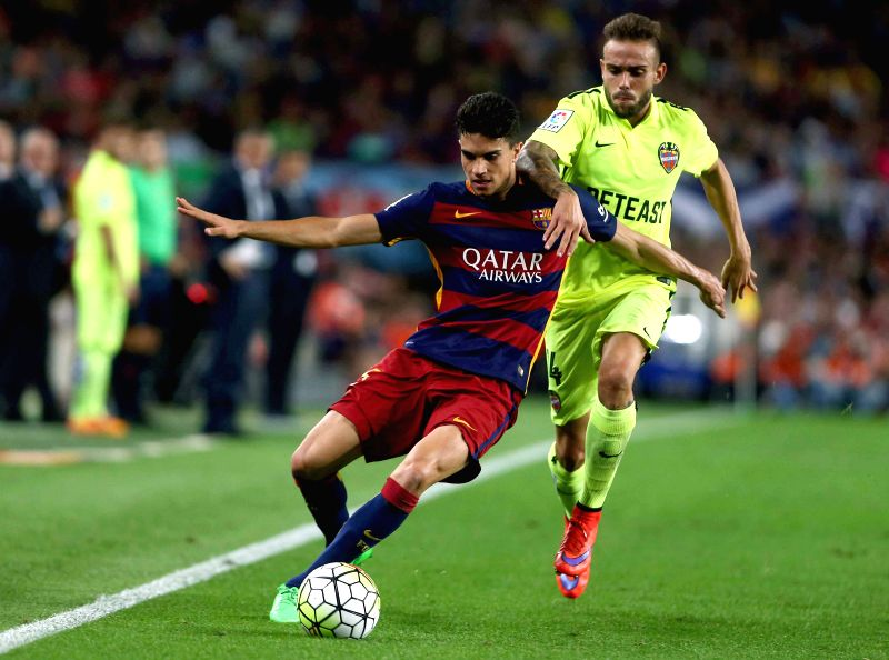 :FC Barcelona's defender Marc Bartra (L) duels for the ball with UD Levante's forward Roger Martí (R) during the Spanish Liga Primera Division soccer match between FC Barcelona and UD ...