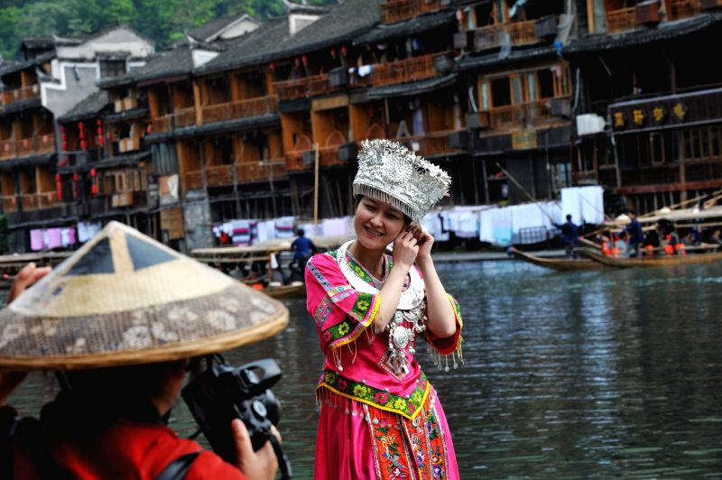 Tourists take photos at the Fenghuang ancient town, in Xiangxi Tujia-Miao Autonomous Prefecture of central China's Hunan Province, April 22, 2014.  Photo: ...