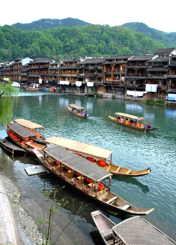 Tourists travel by boats at the Fenghuang ancient town, in Xiangxi Tujia-Miao Autonomous Prefecture of central China's Hunan Province, April 22, 2014.  Photo: ...