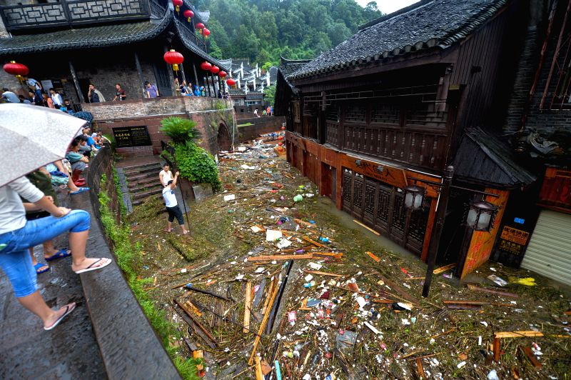 People watch the debris on a street after flood in the historical town of Fenghuang, central China's Hunan province, July 15, 2014. Continuous rain has flooded ...
