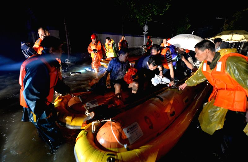 Rescuers try to evacuate victims after a rainstorm in Fenghuang Ancient Town in Fenghuang County, central China's Hunan Province, July 15, 2014.  More than ...