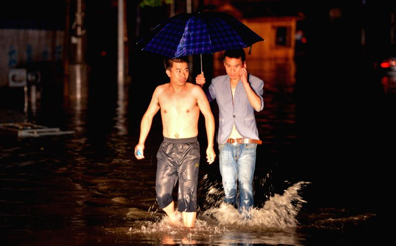 Residents wade through water on a flooded road in Fenghuang Ancient Town in Fenghuang County, central China's Hunan Province, July 15, 2014.  More than 120,000 ...