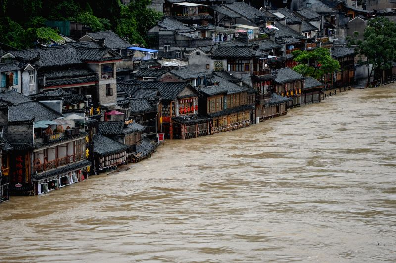 Shops along a river are inundated by flood water in the tourist destination of Fenghuang, central China's Hunan Province, July 16, 2014. Hunan Province has been ..
