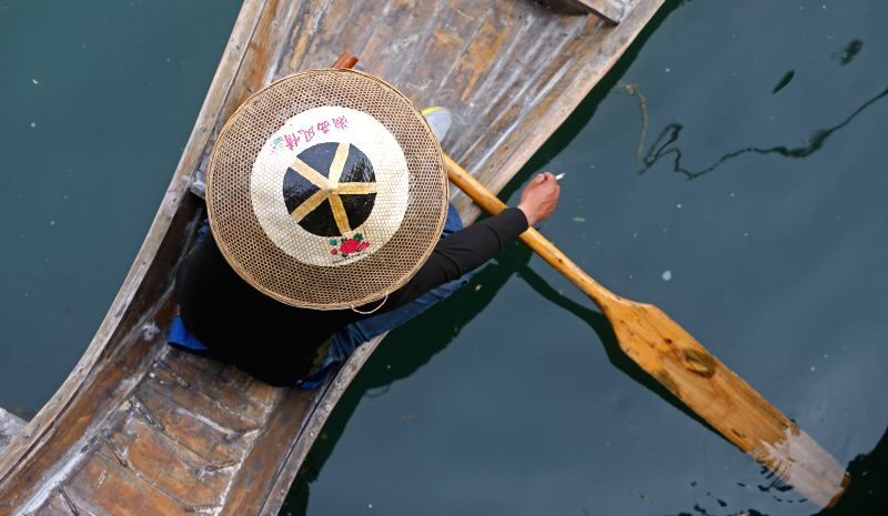 A boatman wearing a bamboo hat as he takes part in a folk festival in the Phoenix (Fenghuang) ancient city, central China's Hunan Province, May 6, 2014. Local ...