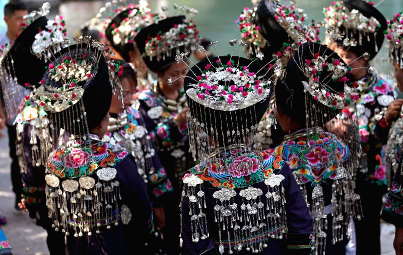 Women of Miao ethnic group wear traditional headdresses as they prepare to take part in a folk festival in the Phoenix (Fenghuang) ancient city, central China's ...