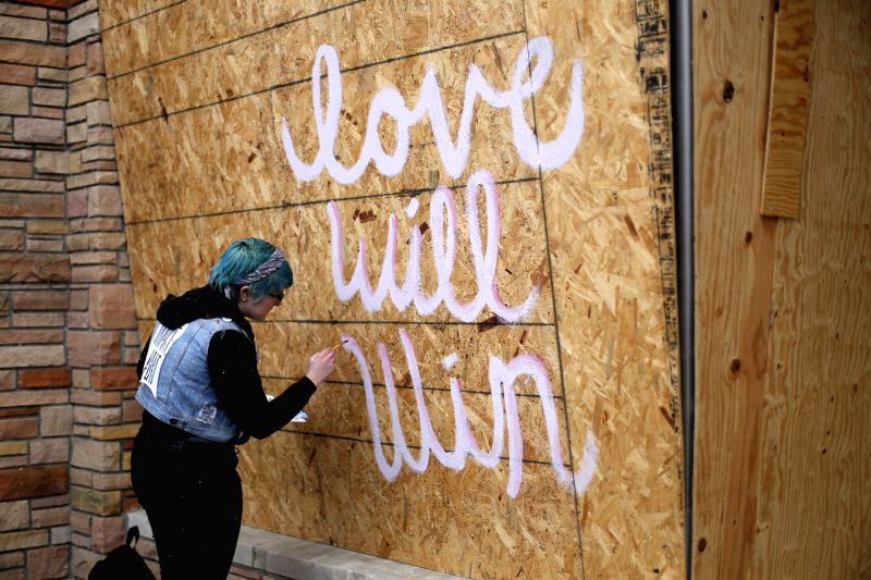 A resident paints mural on the board of a storefront in Ferguson, Missouri, the United States, on Nov. 26, 2014. Missouri Governor Jay Nixon has called in more National Guards to control ...