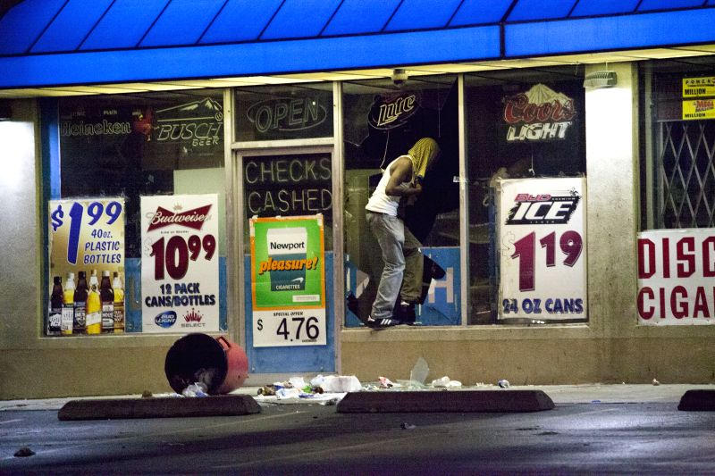 A man loots a Family Dollar store on W. Florissant Avenue, in Ferguson, the United States, Aug. 16, 2014.The situation in Ferguson has been tense since an unarmed .