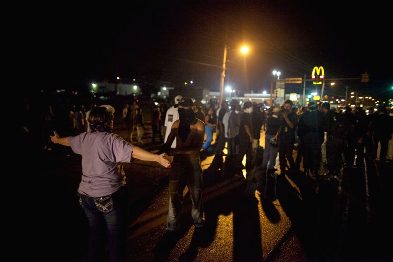 A woman blocks a protester from charging at the police on W. Florissant Avenue, in Ferguson, the United States, Aug. 16, 2014. The situation in Ferguson has been ..