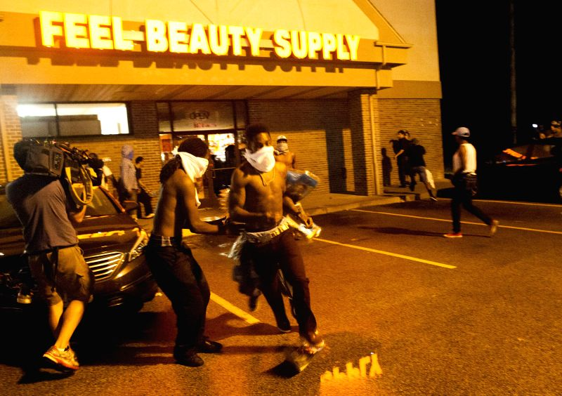 Men haul out a box from a beauty store on W. Florissant Avenue, in Ferguson, the United States, Aug. 16, 2014. The situation in Ferguson has been tense since an ...