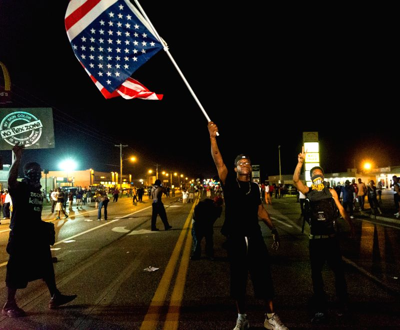 A man waves a national flag of the United States during the protest against police killing of Michael Brown in Ferguson, Missouri, the United States, on Aug. 19, ..