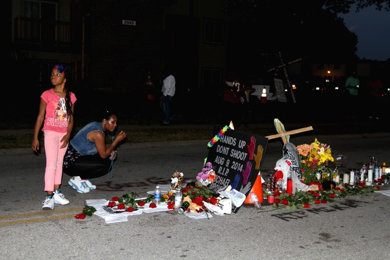A mother and her daughter lay roses at the site where Michael Brown was shot dead in Ferguson, Missouri, the United States, on Aug. 19, 2014. On Aug. 9, ...