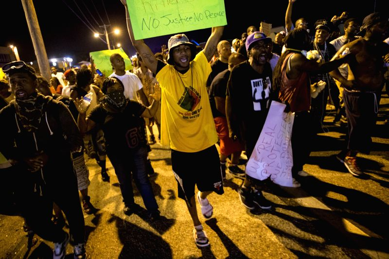 Demonstrators march on the street to protest against police killing of 18-year-old Michael Brown and another 23-year-old black man in Ferguson, Missouri, the ...