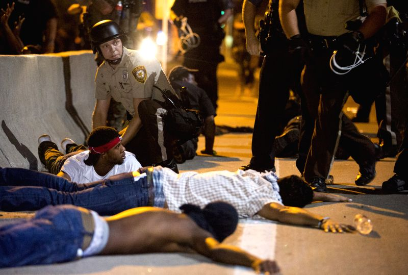 Police officers arrest demonstrators during a protest against police killing of 18-year-old Michael Brown and another 23-year-old black man in Ferguson, Missouri, .