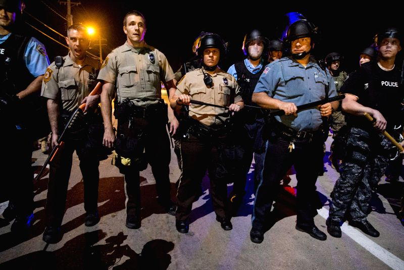 Police officers in riot gear stand guard during a protest against police killing of 18-year-old Michael Brown and another 23-year-old black man in Ferguson, ...