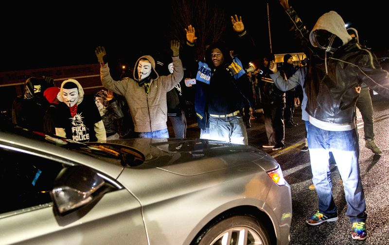 Protesters in masks protest on the street near the Ferguson Police Station in Ferguson, Missouri, the United States, on Nov. 23, 2014, pending the Grand Jury's decision on whether to charge