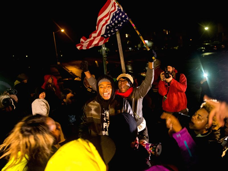 Protesters protest on the street in Ferguson, Missouri, the United States, on Nov. 23, 2014, pending the Grand Jury's decision on whether to charge the police officer killing unarmed ...