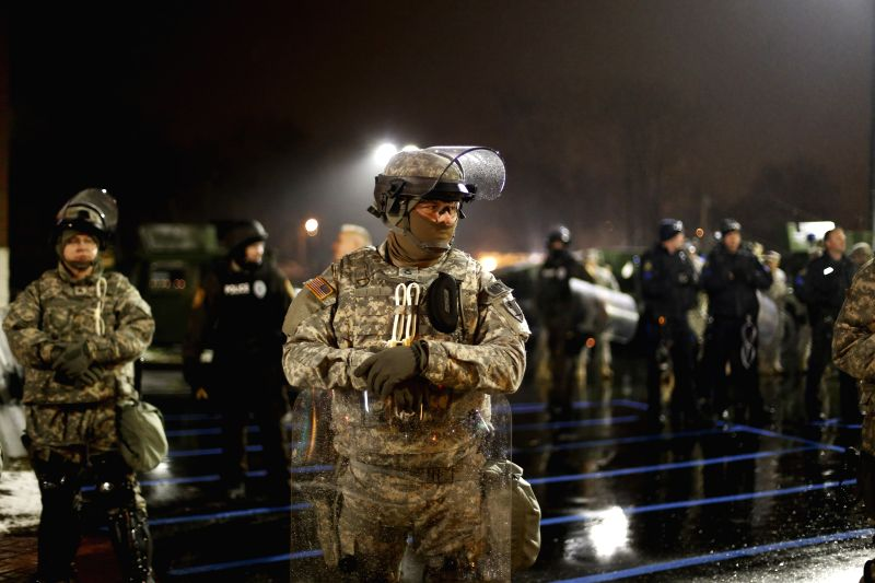 U.S. national guardsmen stand guard outside the Ferguson Police Department, in Ferguson, Missouri, the United States, on Nov. 26, 2014. Missouri Governor Jay Nixon has called in more ...