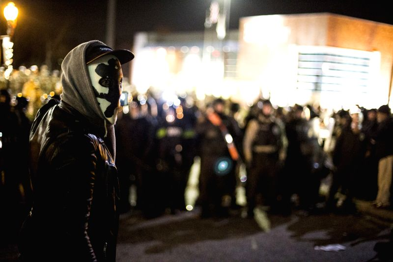 Ferguson (United States): A protester in mask looks back as police come in from behind and box in many protesters near the Ferguson PD Station in Ferguson, Missouri, the United States, on Nov. 28, ...