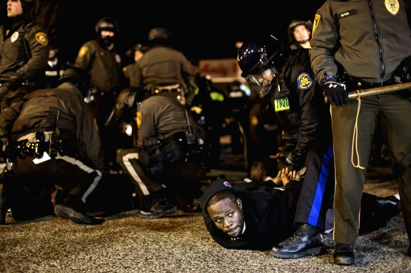 Ferguson (United States):  Policemen arrest a protester in front of the Ferguson PD Station in Ferguson, Missouri, the United States, on Nov. 28, 2014. Police arrested 15 people Friday night as about