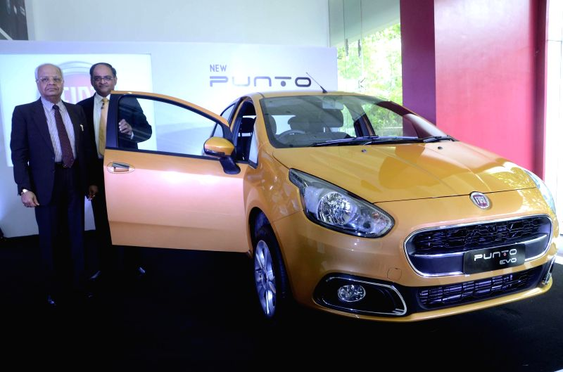 FIAT Chrysler Vice-President, Sales and Dealer Development Ravi Bhati and Chairman and Managing Director of Esskay Motors, C. K. Parkash during the launch of Fiat's Punto EVO in Mumbai on Aug 8, ...