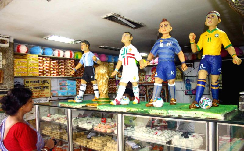 Figurines of footballers playing 2014 FIFA World Cup on display at a sweet shop in Howrah on June 20, 2014.