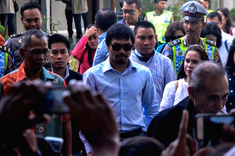 Filipino boxing icon Manny Pacquiao (C) walks during his visit at Wirogunan prison in Yogyakarta, Indonesia, July 10, 2015. Manny Pacquiao visited his compatriot ...