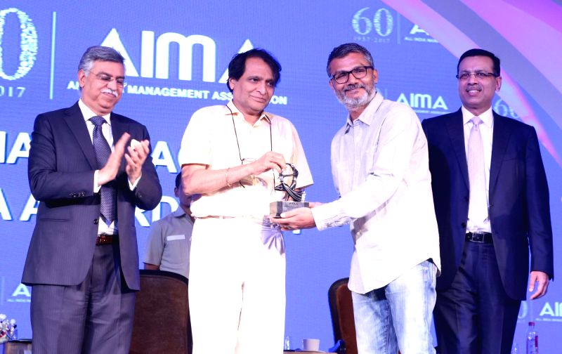Filmmaker and Screenwriter Nitesh Tiwari receives Director of the Year award from Union Railway Minister Suresh Prabhu at the AIMA Awards ceremony in New Delhi, on April 27, 2017. - Suresh Prabhu