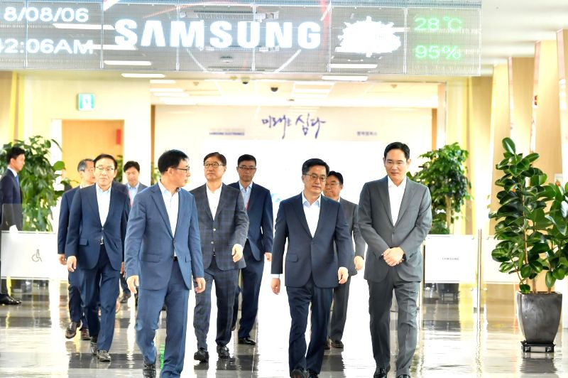 Finance Minister Kim Dong-yeon (2nd from R), escorted by Lee Jae-yong (R), the de facto chief of Samsung Group, looks around Samsung Electronics Co.'s plant in Pyeongtaek, some 70 km ... - Kim Dong