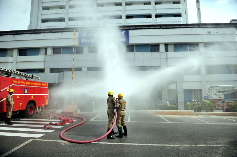 Fire Brigade personnel during a mock drill being conducted at the premises of Manipal Hospital in Bangalore on June 25, 2014.
