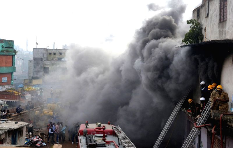 Fire brigade personnel try hard to douse a fire that broke out in a car godown near Kalasipalyam  in Bangalore on July 31, 2014.