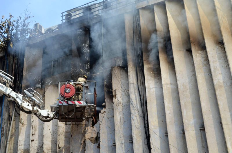 Fire fighter try hard to douse a fire that broke out inside an NIIT (National Institute of Information Technology) computer training centre located in A-block of Connaught Place of Delhi on Aug 25, ..