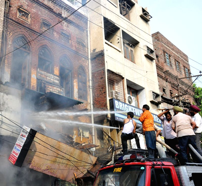 Fire fighters try hard to douse a fire that broke out in a chemical shop in Amritsar on July 16, 2014.
