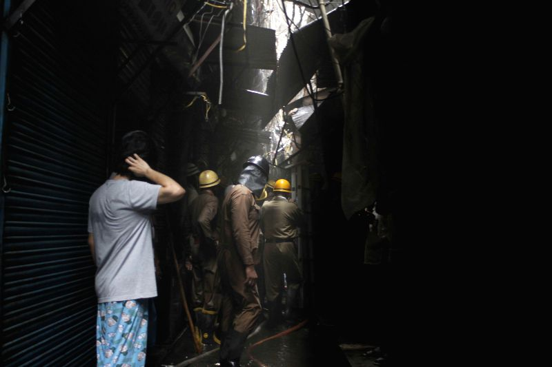 Fire fighters try to break into a shop so as to control a fire that broke out in Sadar Bazar market of New Delhi on May 4, 2014.