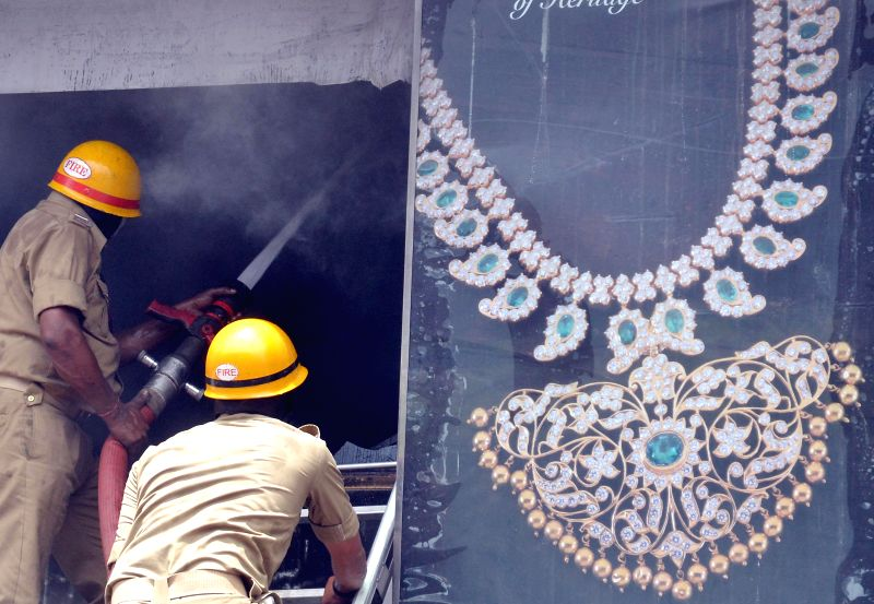Fire fighters try to douse a fire that broke out at a jewellery showroom situated on Bangalore's MG Road on July 3, 2014.