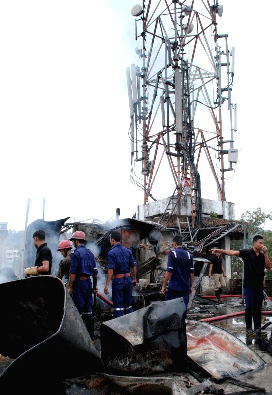 Fire fighters try to douse the fire that broke out at a mobile tower transformer due to short circuit setup at the top of a building at Sundarpur area in Guwahati on August 02, 2014.