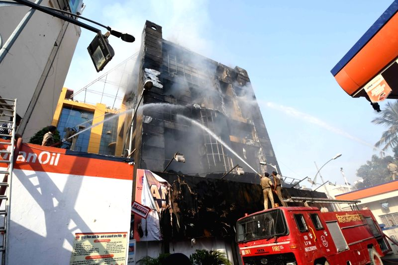 Firefighters douse a fire that broke out at a shopping mall located at Boring Road in Patna on May 20, 2017.