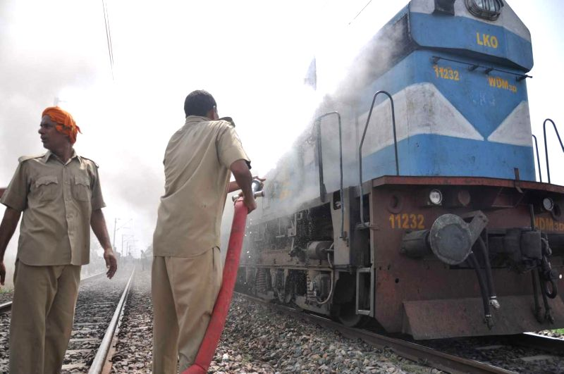 Firefighters douse a fire that broke-out in a rail engine near Gomti Nagar in Lucknow on July 2, 2014.