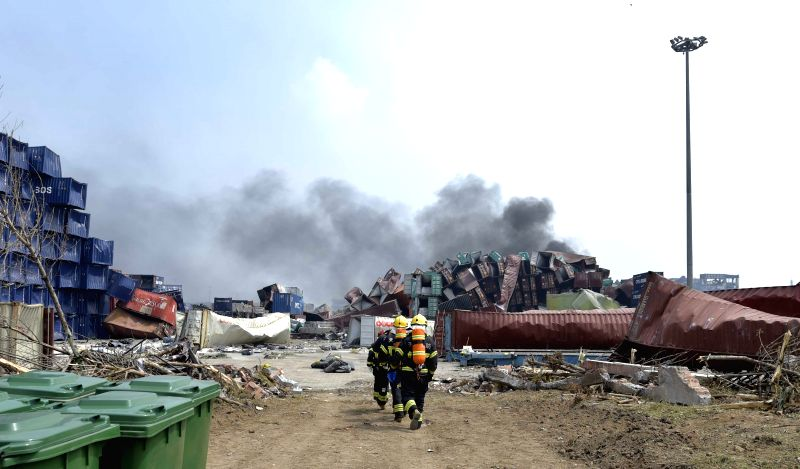 Firefighters examine the explosion site in Tianjin, north China, Aug. 14, 2015. The enormous blasts, which occurred late Wednesday night, killed at least 50 people, ...